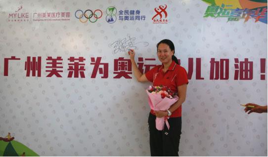 """张洁雯在""""万人签名墙""""上签字,签名墙将在奥运开幕后送至巴西参赛的中国奥运代表团为奥运健儿加油。"""